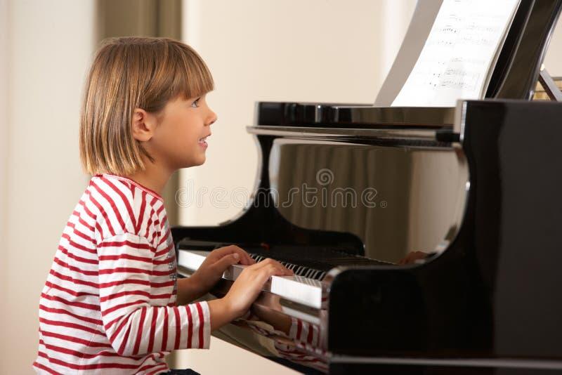 Rapariga que joga o piano grande fotografia de stock royalty free