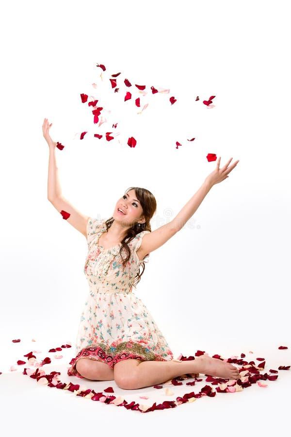 Rapariga que lanç a pétala cor-de-rosa foto de stock