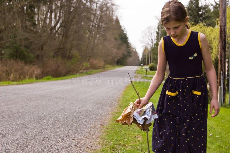 Rapariga que limpa o ambiente da borda da estrada imagem de stock royalty free