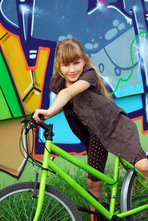 Rapariga que monta a bicicleta foto de stock