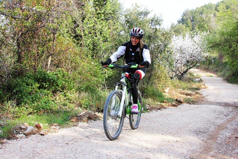Rapariga que monta uma bicicleta fotografia de stock