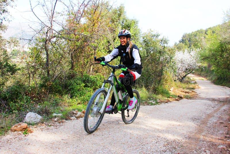 Rapariga que monta uma bicicleta imagens de stock