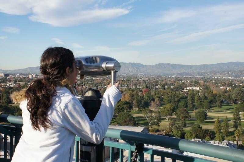 Rapariga que olha através de um telescópio fotografia de stock royalty free
