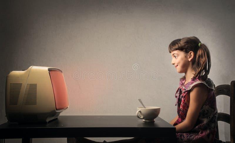 Rapariga que presta atenção à tevê fotografia de stock
