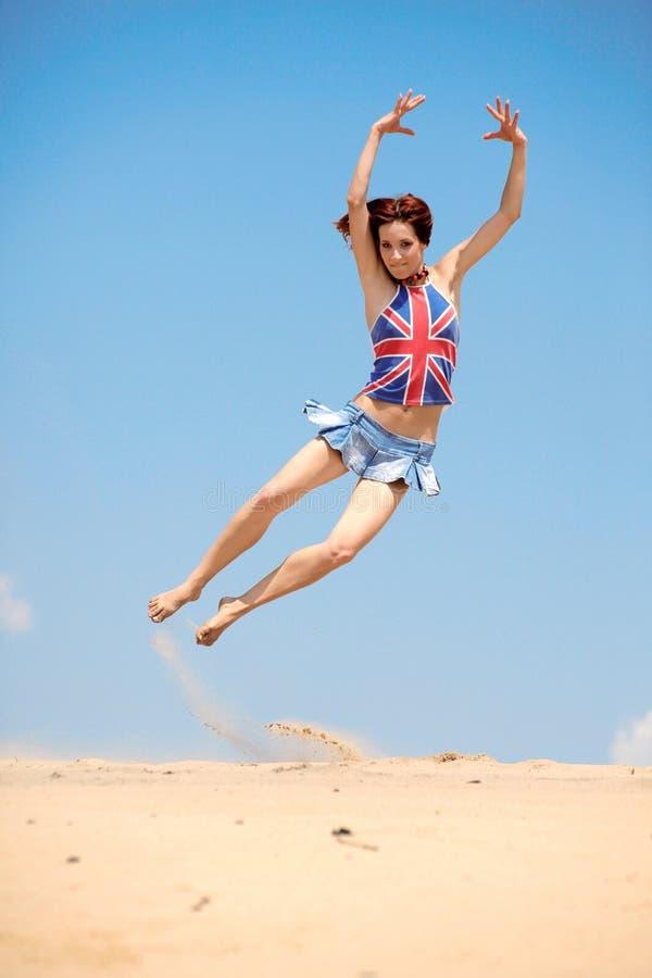 A rapariga que salta em um fundo do céu azul fotografia de stock