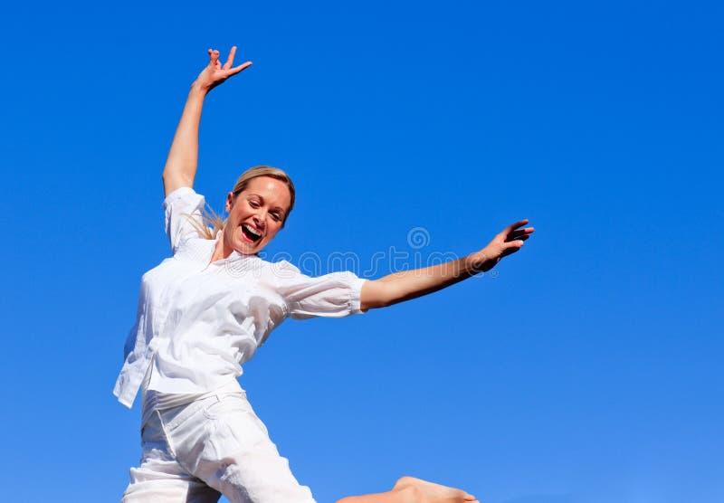 A rapariga que salta em um parque fotografia de stock