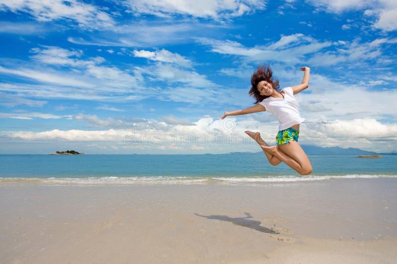 A rapariga que salta graciosa na praia foto de stock royalty free