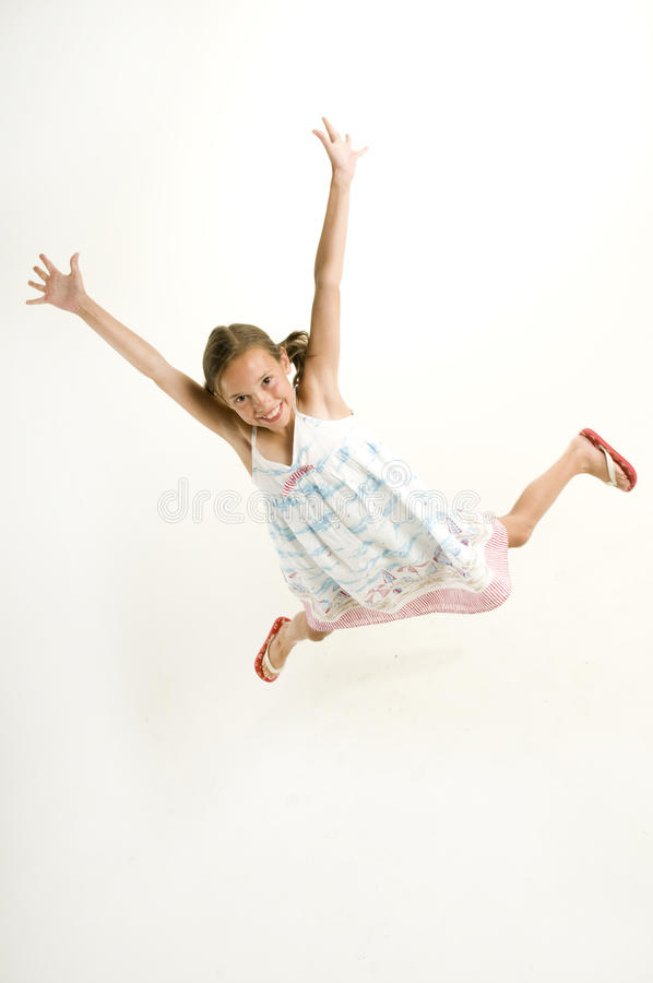 A rapariga que salta para a alegria fotografia de stock