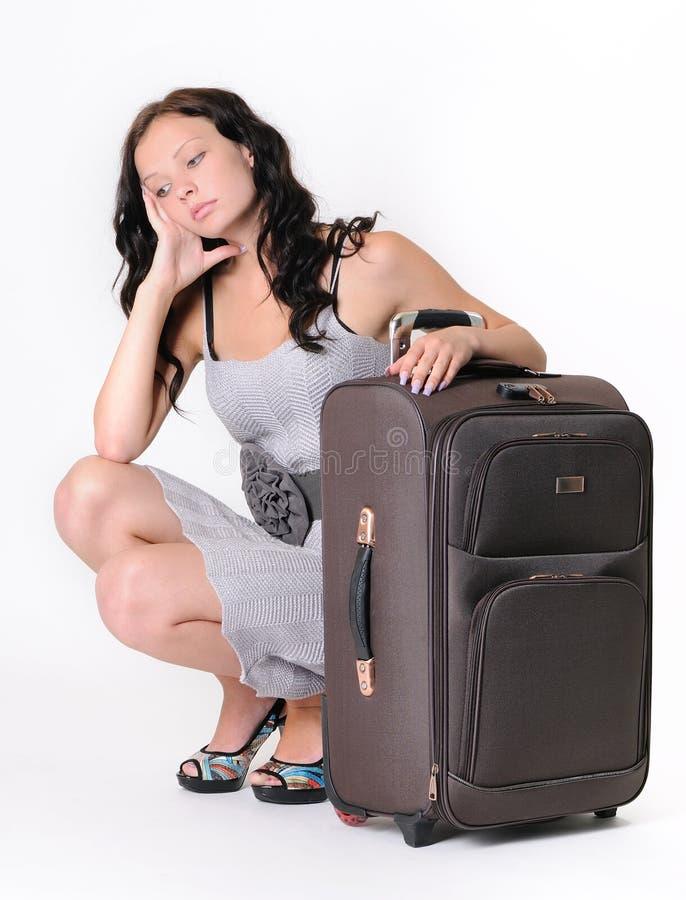 Rapariga que senta-se com uma mala de viagem fotografia de stock