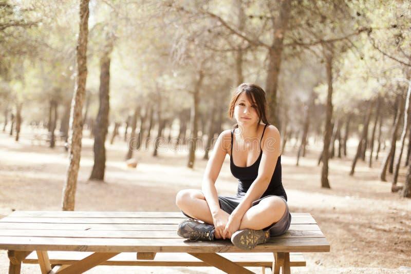 Rapariga que senta-se em uma tabela de madeira fotos de stock