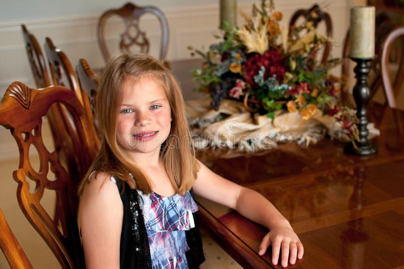 Rapariga que senta-se na tabela de jantar de madeira imagens de stock royalty free