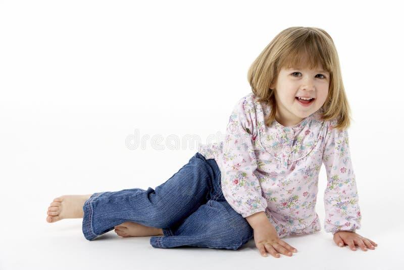 Rapariga que senta-se no estúdio foto de stock