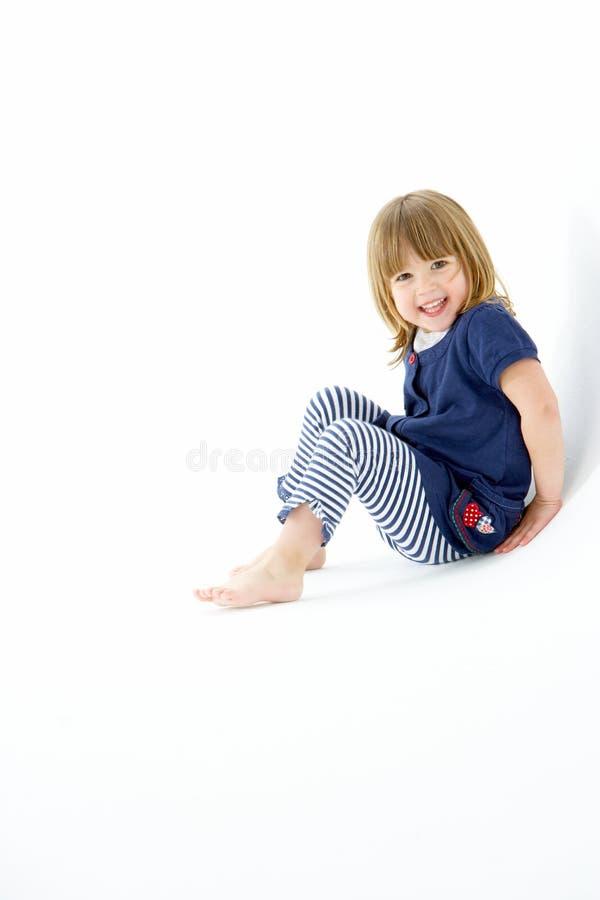 Rapariga que senta-se no estúdio branco imagens de stock royalty free