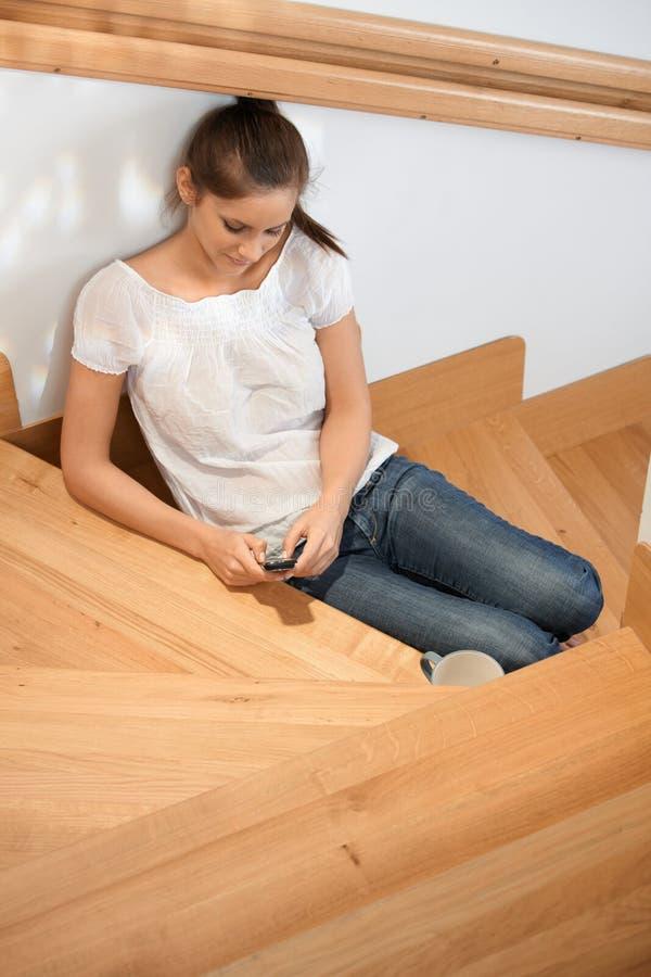 Rapariga que texting em escadas fotografia de stock