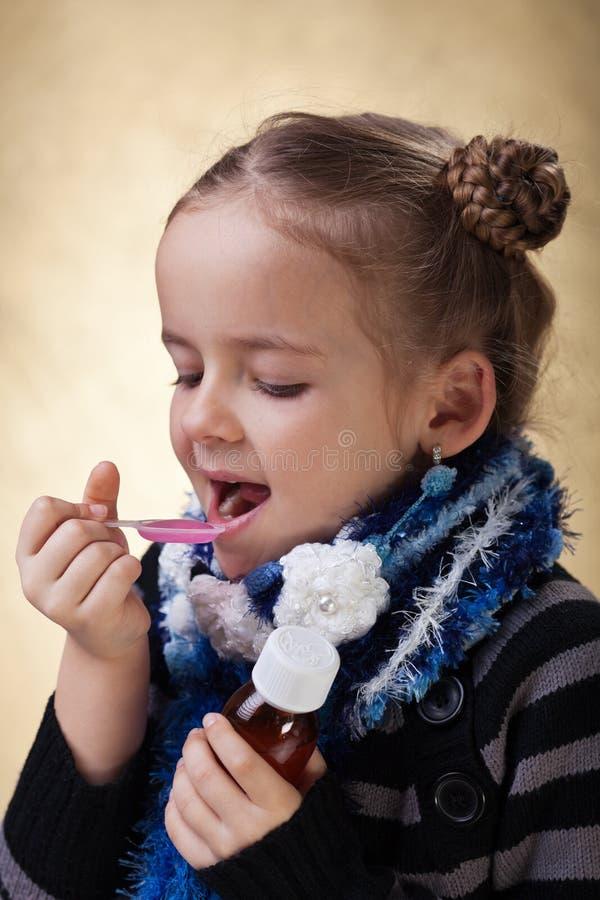 Rapariga que toma a medicina da tosse fotografia de stock