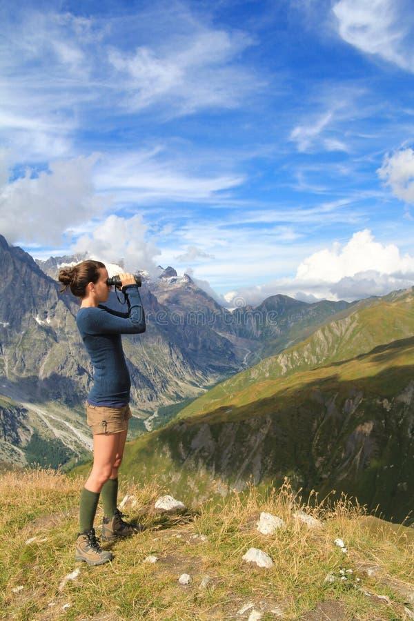 Rapariga sobre o vale da doninha com binocular foto de stock