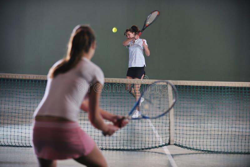 Raparigas que jogam o jogo do tênis interno imagem de stock royalty free