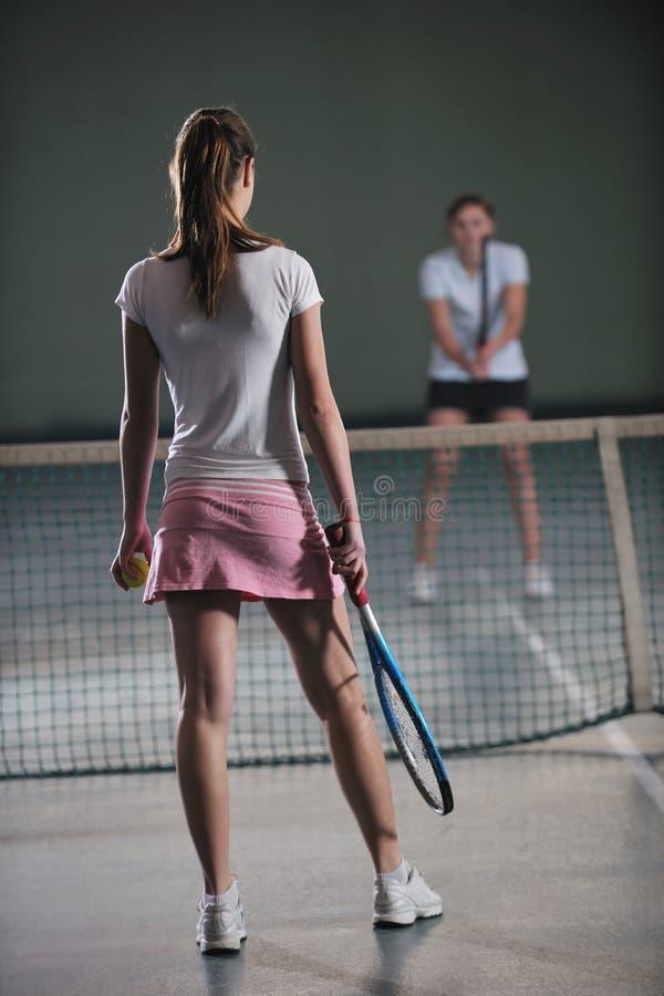 Raparigas que jogam o jogo do tênis interno imagem de stock