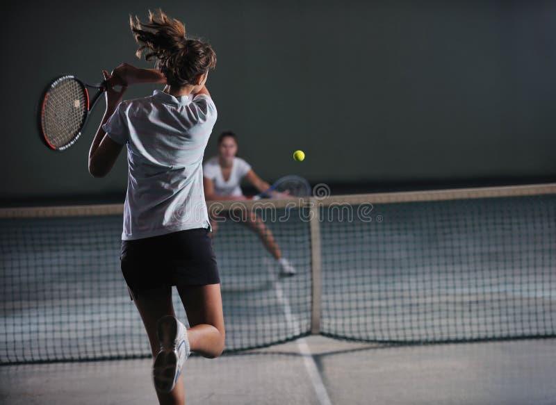 Raparigas que jogam o jogo do tênis interno imagens de stock