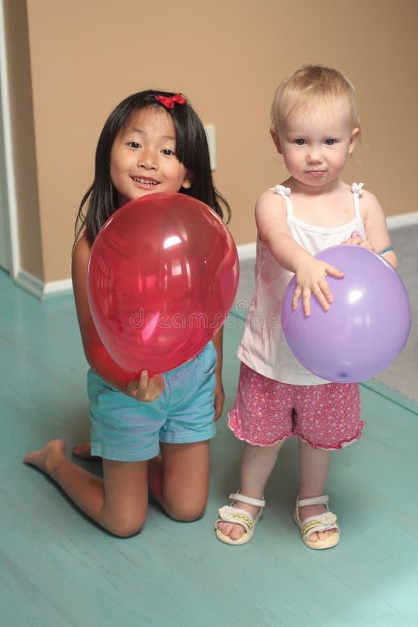 Raparigas que prendem balões imagem de stock royalty free