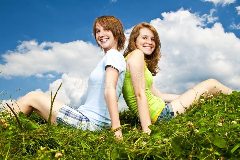 Raparigas que sentam-se no prado imagens de stock