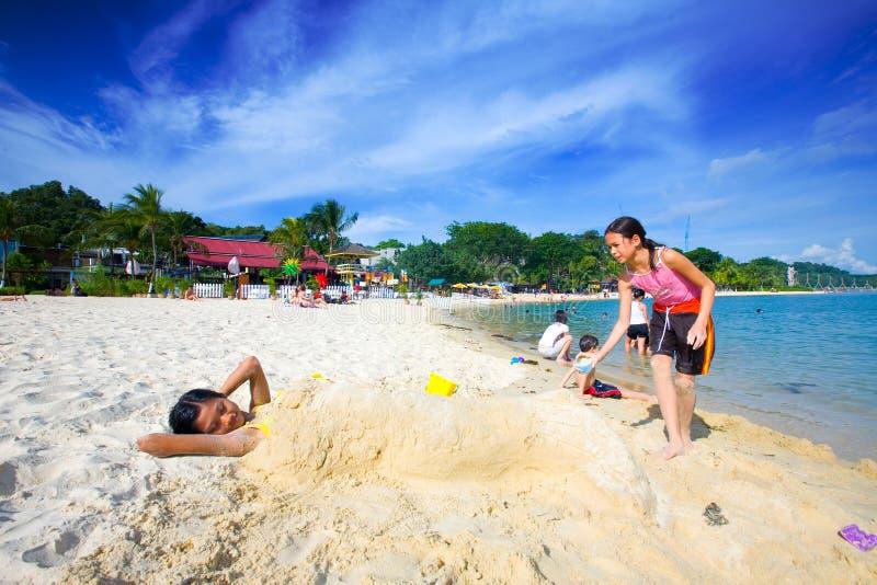 Raparigas que têm o divertimento jogar a sereia da areia fotografia de stock royalty free