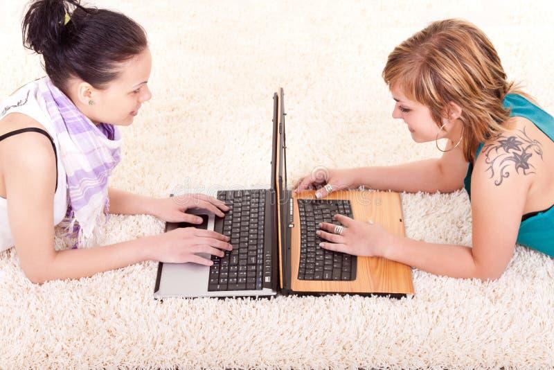 Raparigas que trabalham em portáteis fotos de stock