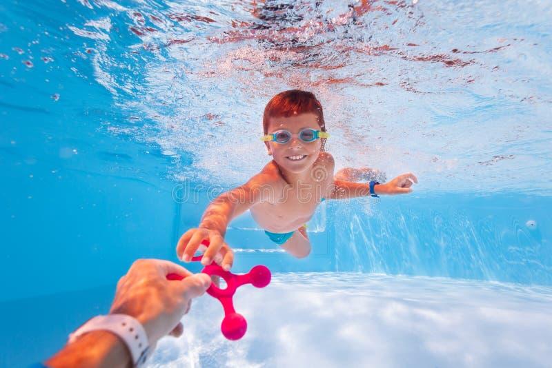Rapaz nada debaixo d'água levando brinquedos do pai imagens de stock