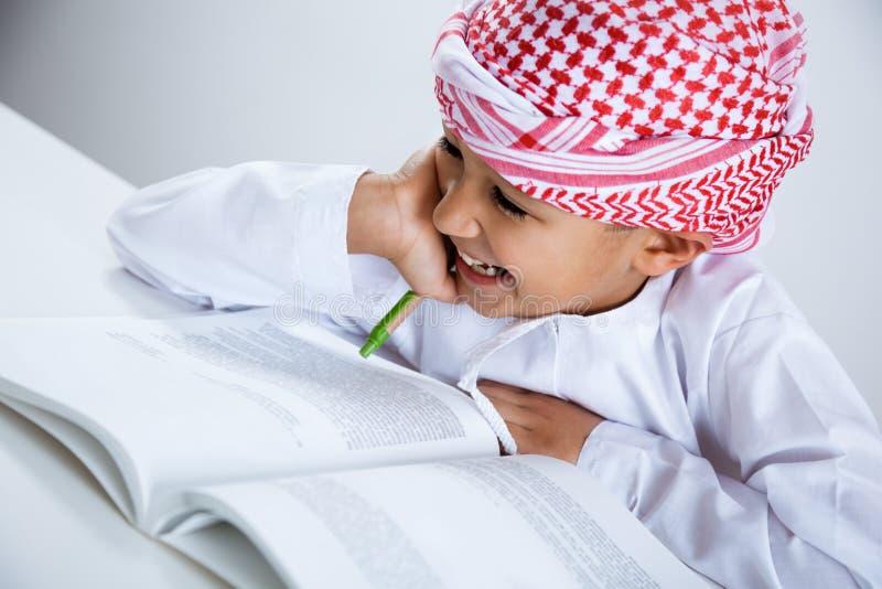 Rapaz pequeno árabe que faz trabalhos de casa foto de stock royalty free