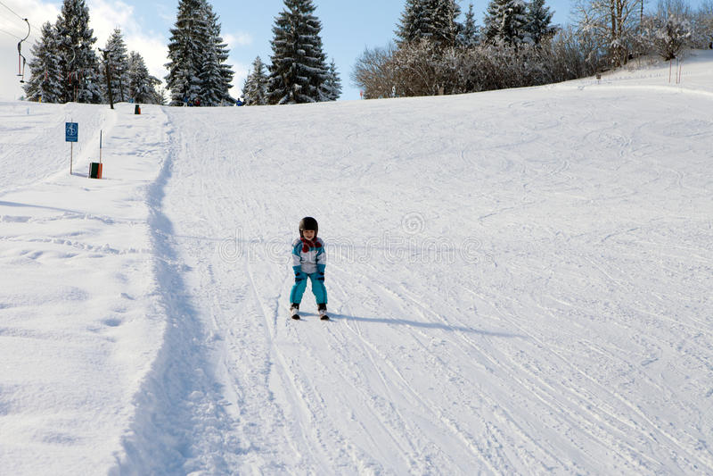 Rapaz pequeno adorável com casaco azul e um capacete, esquiando fotografia de stock royalty free