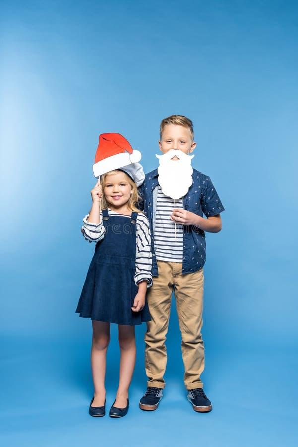 rapaz pequeno adorável e menina com chapéu de Santa e barba da falsificação que sorriem na câmera foto de stock