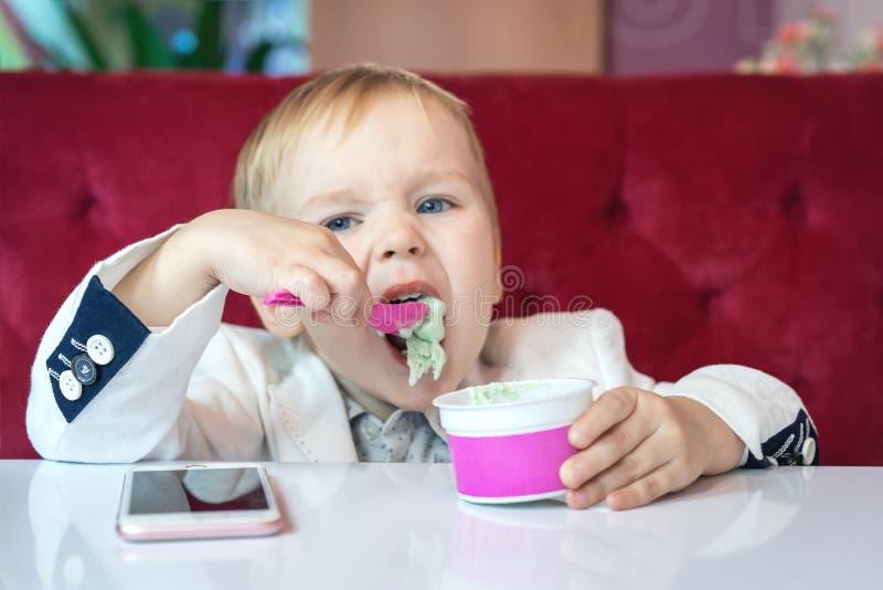 Rapaz pequeno adorável em um terno de negócio do ` s do homem de negócios com pressa que come o gelado no restaurante durante o a imagem de stock