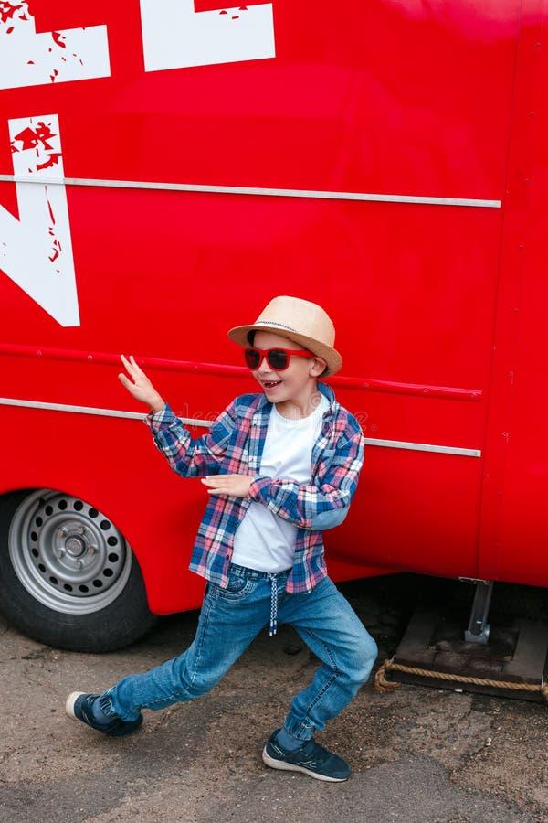 Rapaz pequeno adorável na roupa na moda e na dança vermelha dos óculos de sol exteriores imagens de stock