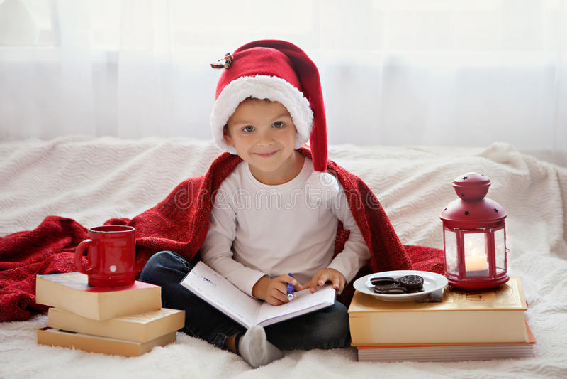 Rapaz pequeno adorável, preparando-se por feriados do Natal foto de stock