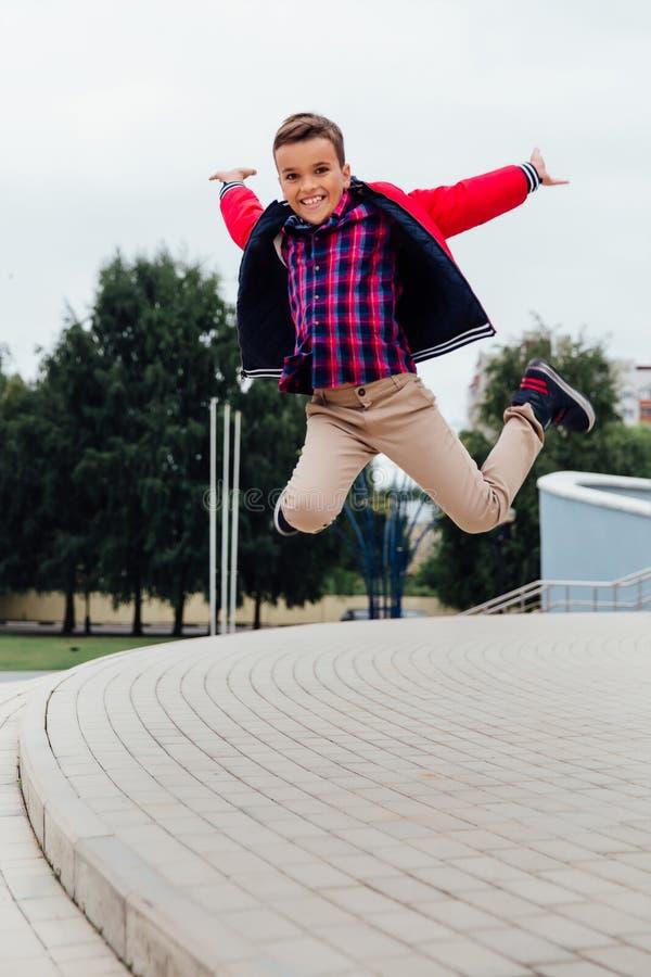Rapaz pequeno adorável que salta no ar em escadas em uma cidade, vestindo um casaco de cabedal marrom fotos de stock