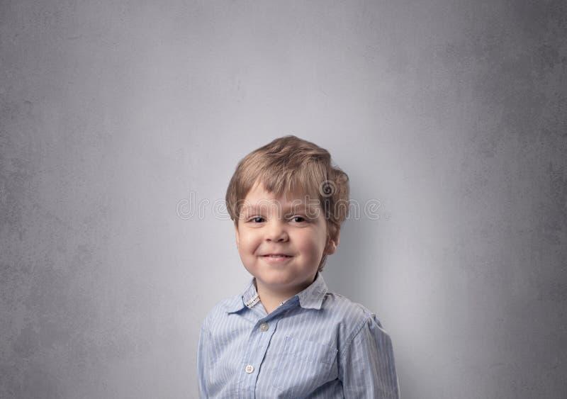 Rapaz pequeno ador?vel na frente de uma parede vazia foto de stock royalty free