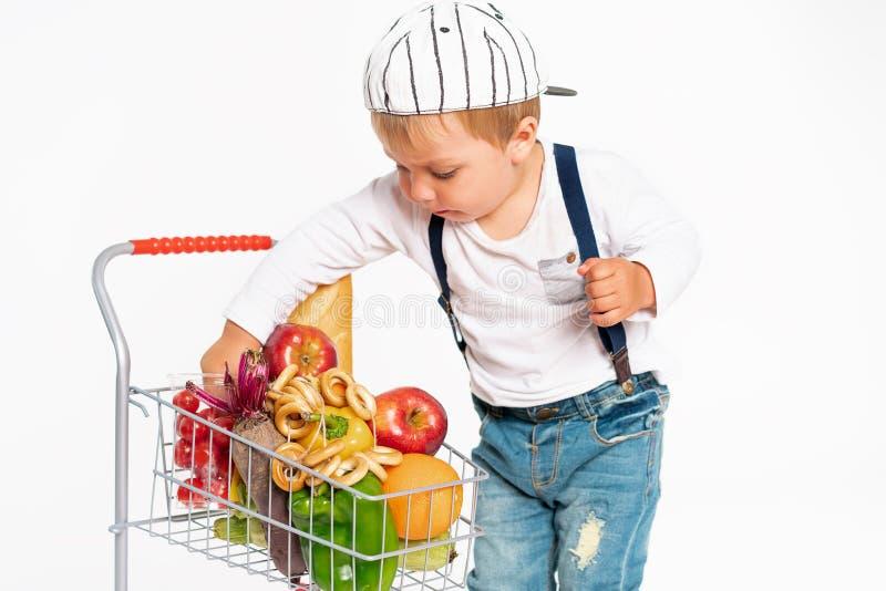 Rapaz pequeno alegre na roupa ocasional que está no estúdio com a cesta saudável do alimento Compra, desconto, conceito da venda fotografia de stock royalty free