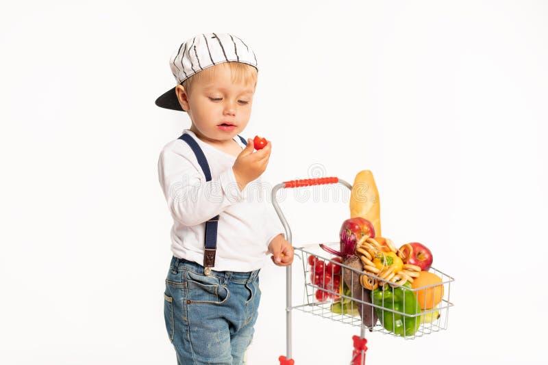 Rapaz pequeno alegre na roupa ocasional que está no estúdio com a cesta saudável do alimento Compra, desconto, conceito da venda fotos de stock royalty free