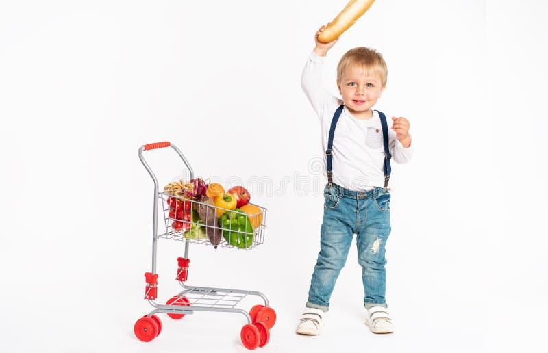Rapaz pequeno alegre na roupa ocasional que está no estúdio com a cesta saudável do alimento Compra, desconto, conceito da venda fotografia de stock