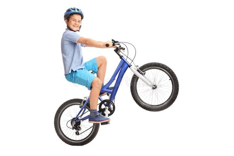 Rapaz pequeno alegre que executa um wheelie com sua bicicleta fotografia de stock royalty free