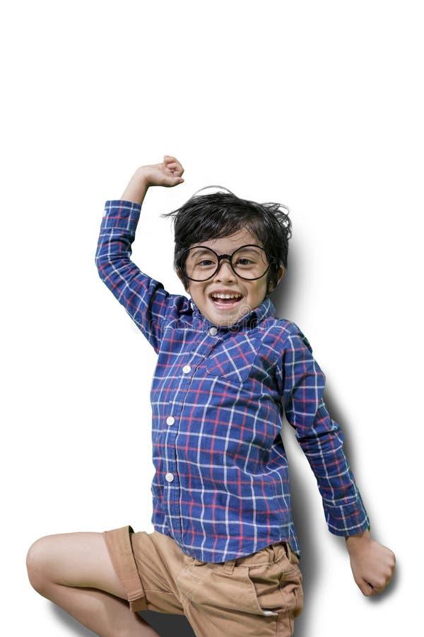 Rapaz pequeno alegre que salta no estúdio imagem de stock