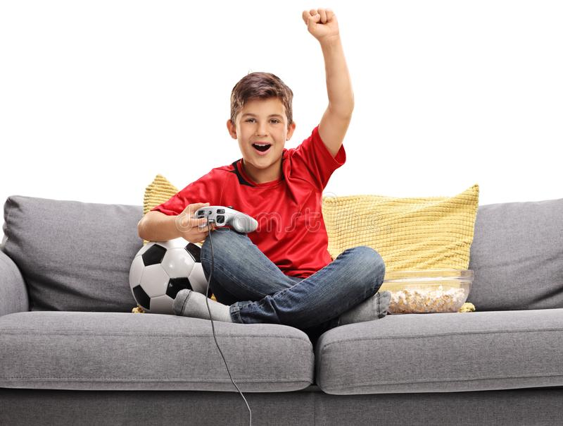 Rapaz pequeno alegre que senta-se em um sofá e que joga um jogo de vídeo do futebol fotografia de stock