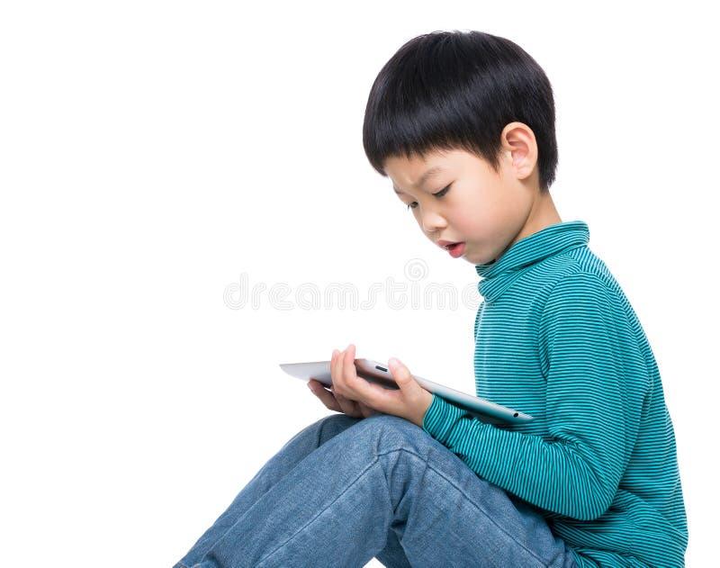 Rapaz pequeno asiático que olha na tabuleta fotos de stock royalty free