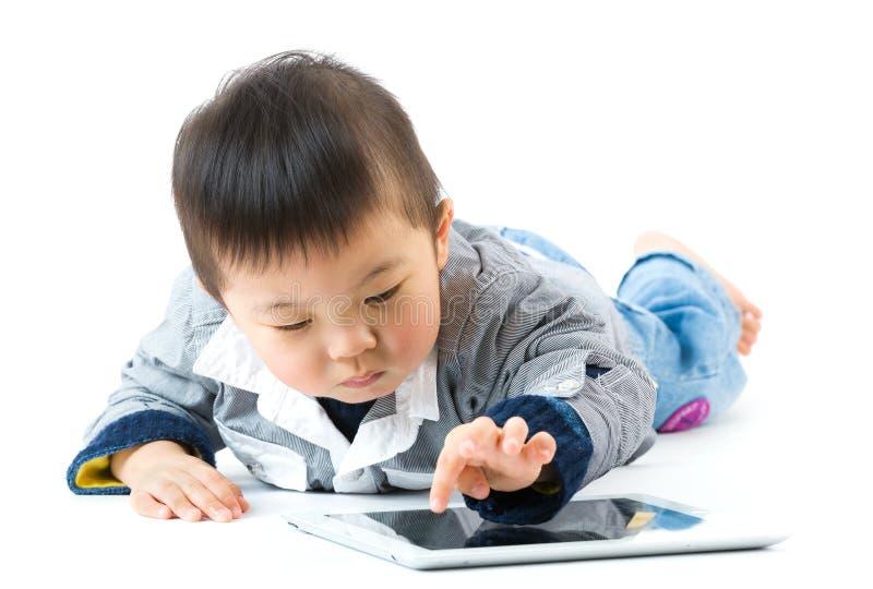 Rapaz pequeno asiático que usa a tabuleta digital fotos de stock