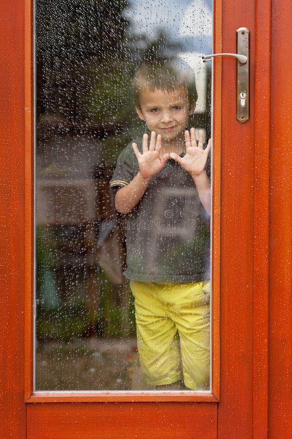 Rapaz pequeno atrás da janela na chuva imagem de stock