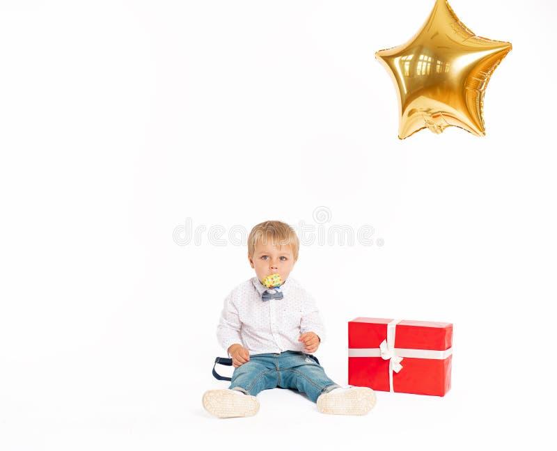 Rapaz pequeno bonito, calças de brim e camisa, estando perto do presente e fundindo no acordo do aniversário fotos de stock royalty free