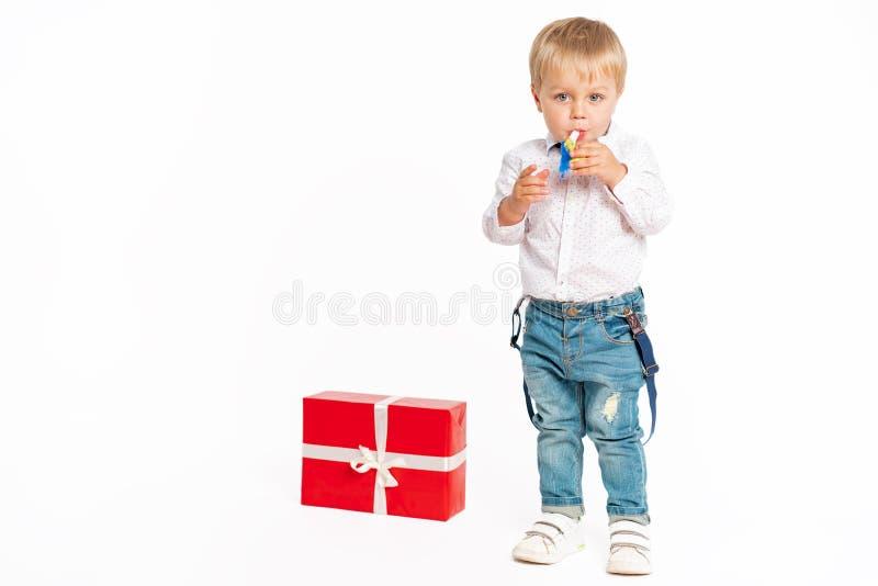 Rapaz pequeno bonito, calças de brim e camisa, estando perto do presente e fundindo no acordo do aniversário fotografia de stock