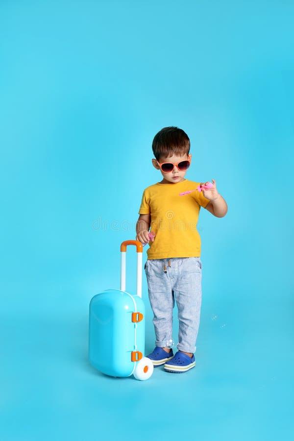 Rapaz pequeno bonito com óculos de sol e mala de viagem fotos de stock