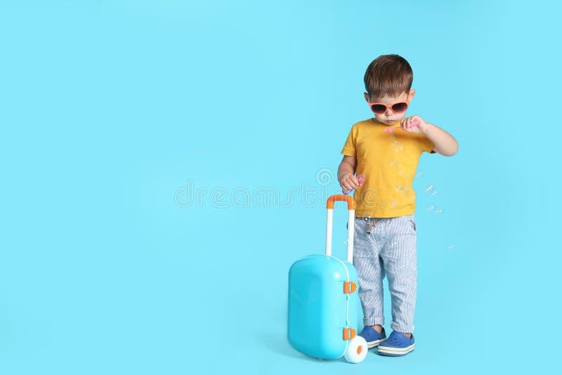 Rapaz pequeno bonito com óculos de sol e mala de viagem no fundo azul foto de stock royalty free