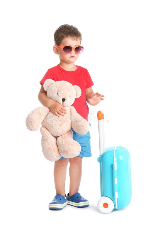 Rapaz pequeno bonito com brinquedo e a mala de viagem azul foto de stock